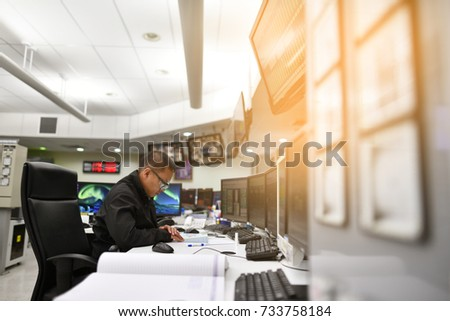 Control room operator checking process in power plant.