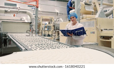 Controller checking conveyor with candies. Young woman in uniform holding folder and inspecting conveyor belt with fresh candies in confectionery factory. Candy factory.
