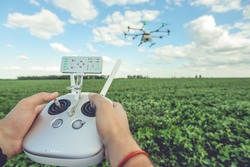Controlling a remote Octocopter drone. Drone flight remote controller in man hands. Agriculture drone flies over the green field.