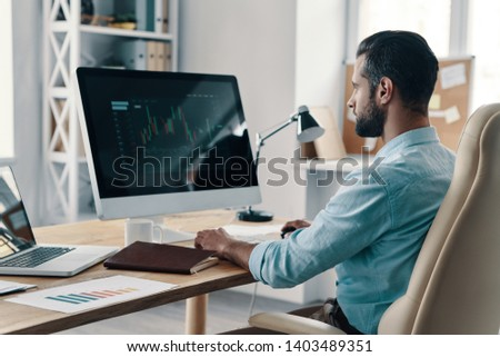 Controlling capital. Young modern businessman analyzing data using computer while sitting in the office