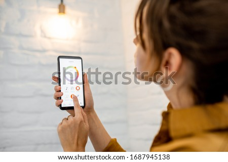 Photo of  Controlling light bulb temperature and intensity with a smartphone application. Concept of a smart home and managing light with mobile devices