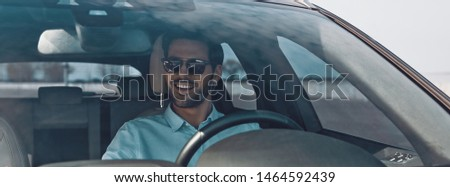 Convenience way to travel. Handsome young man smiling while driving a status car #1464592439