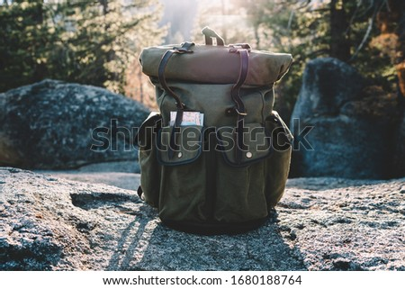 Convenient backpack with map equipment for active leisure tourism in national park with forests, khaki rucksack with roll top and pockets for transporting stuff on hiking Stockfoto ©
