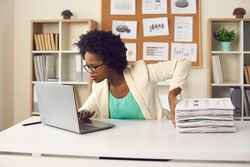 Convenient electronic bookkeeping vs stacks of papers. Secretary or financial accountant organizing digital documents on computer. Young woman sitting at office desk and doing paperwork on laptop