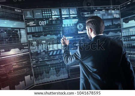 Convenient screen. Calm clever enthusiastic programmer carefully touching the transparent screen while being in his modern office and working at the new program #1041678595
