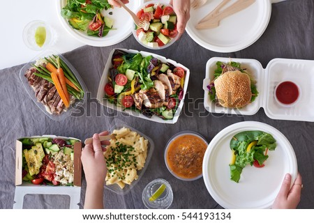 Convenient takeaway takeout food for party, overhead spread of assorted food with hands serving up