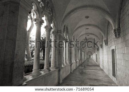 Converging lines of historic, stone cloister of  franciscan monastery in Dubrovnik, Croatia,black and white