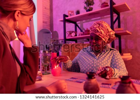Conversation. African american plump fortune-teller wearing a huge ring pointing to a cup while explaining the cards meaning