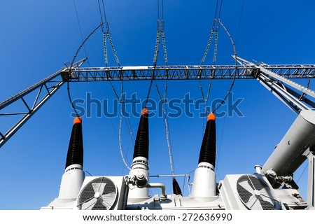 Converter transformer in electrical substation (transformer station) with ceramic insulators and cooling ventilation. Blue sky background, power, energy and electricity concept.
