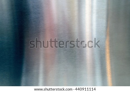 Convex polished shiny steel metal surface with multicolored reflections and glare