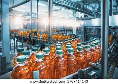 Conveyor belt, juice in bottles, beverage factory interior in blue color, industrial production line.