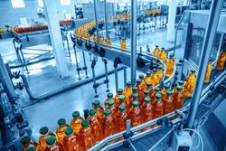 Conveyor belt, juice in bottles on beverage plant or factory interior in blue color, industrial production line, toned