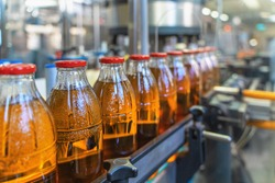Conveyor belt, juice in bottles on beverage plant or factory interior, industrial production line, selective focus.