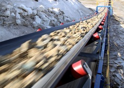 Conveyor belt moves ore from the quarry for processing. Blurred foreground