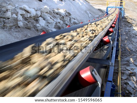 Conveyor belt moves ore from the quarry for processing. Blurred foreground ストックフォト ©