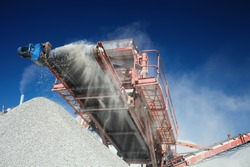 Conveyor belt of a working mobile crusher machine, close-up, with blown away by the wind white stone dust against a blue sky.