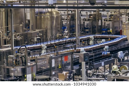 Conveyor belt of brewery production line . Beer polyethylene PET bottles are moving on conveyor.