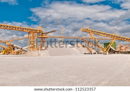 Conveyor on site at gravel pit in front of blue sky with clouds - stock photo
