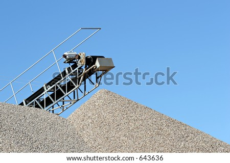 conveyor over heaps of gravel at an industrial cement plant