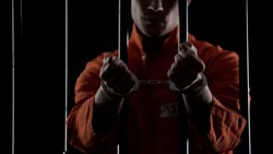 Convicted man showing handcuffs, standing behind prison bars, lawbreaking
