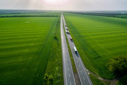 convoys with cargo. trucks on the higthway sunset. cargo delivery driving on asphalt road along the green fields. seen from the air. Aerial view landscape. drone photography.