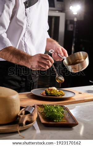 Cook adding some sauce to dish. Cropped chef preparing food, meal, in kitchen, chef cooking, Chef decorating dish, closeup