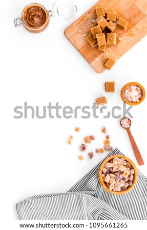 Cook caramel sauce. Melted caramel in glass jar, caramel cubes on cutting board, sugar and salt on white background top view space for text #1095661265