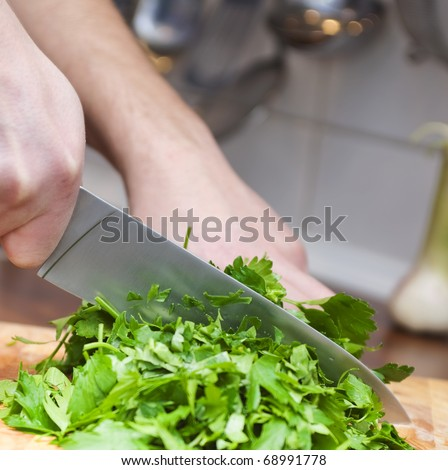 Cook chops fresh parsley with a knife
