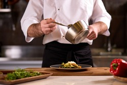 Cook dressing salad with sauce, pouring sauce into plate, finishing cooking of meal in restaurant kitchen, cropped man in apron at work