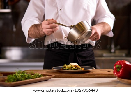 Cook dressing salad with sauce, pouring sauce into plate, finishing cooking of meal in restaurant kitchen, cropped man in apron at work Stok fotoğraf ©