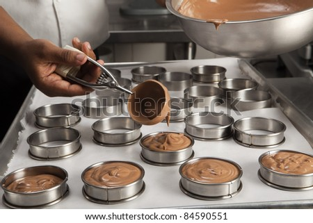 Cook filling the molds with the chocolate mousse