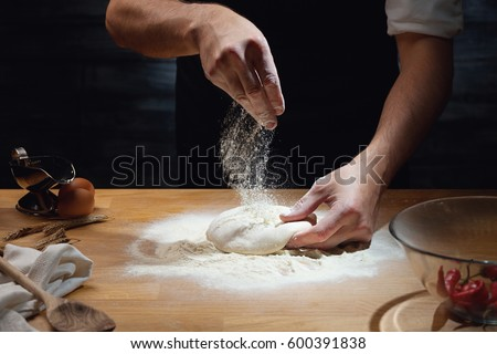Cook hands kneading dough, sprinkling piece of dough with white wheat flour. Low key shot, close up on hands, some ingredients around on table.