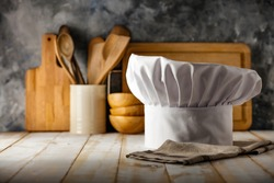 Cook hat on board in kitchen and free space for your decoration.Copy space for your composition.