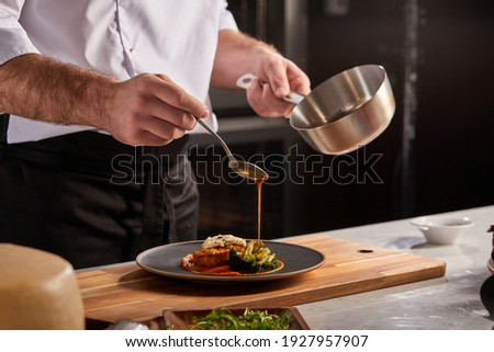 Cook in apron adding some sauce to dish. Cropped chef preparing food, meal, in kitchen, chef cooking, Chef decorating dish, closeup
