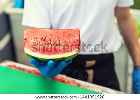 Cook in rubber gloves holding in hand and offering big piece of fresh tasty juicy sliced watermelon for hotel guests at tropical resort outdoors #1441051520