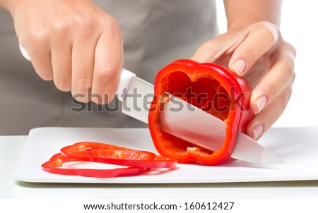 Cook is chopping bell pepper, closeup shoot, isolated over white