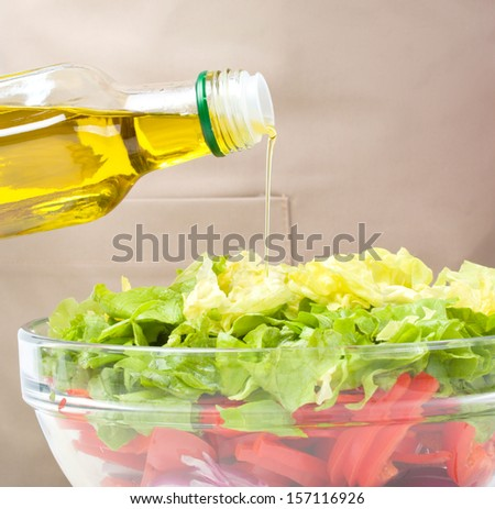 Cook is pouring olive oil into fresh summer salad, closeup shoot