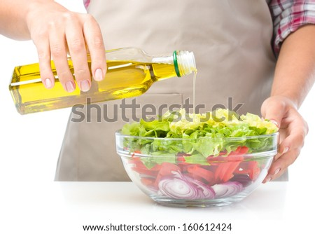 Cook is pouring olive oil into fresh summer salad, closeup shoot, isolated over white