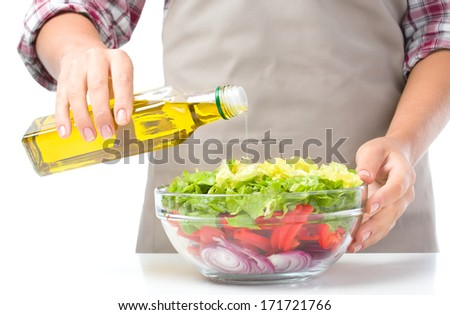 Cook is pouring olive oil into fresh summer salad, closeup shoot, isolated over white - stock photo