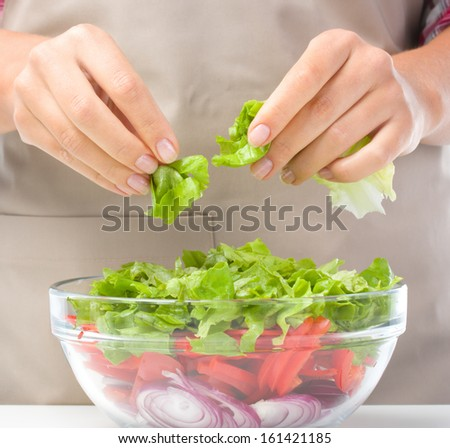 Cook is tearing lettuce while making fresh summer salad, closeup shoot