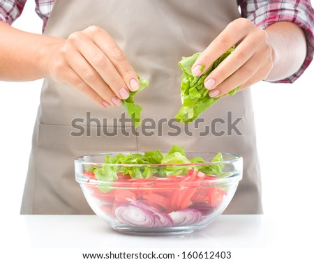 Cook is tearing lettuce while making fresh summer salad, closeup shoot, isolated over white