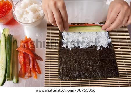 Cook making  Japanese sushi rolls