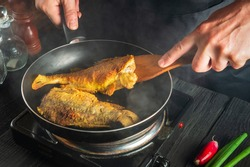 Cook or chef prepares fish in the restaurant kitchen. Boil or fry crucian carp in pan. The idea of a delicious fish diet