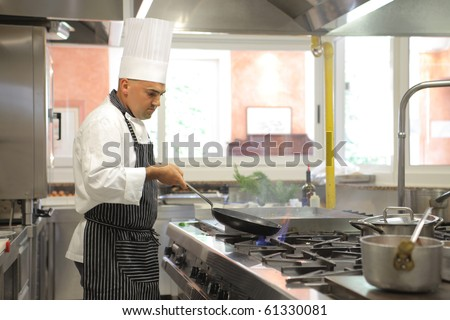 Cook preparing food in a restaurant kitchen - stock photo