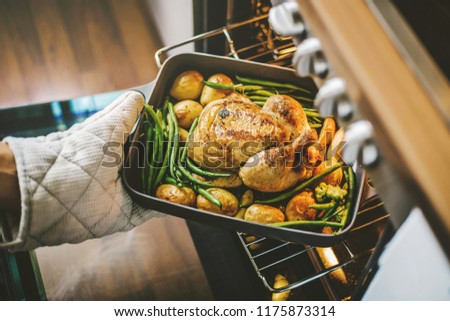Cook taking ready fried baked chicken with vegetables from the oven. Home cooking concept.