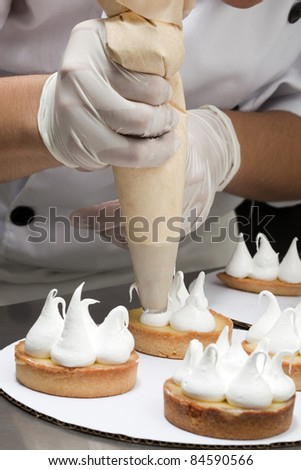 Cook topping the tartlets with meringue
