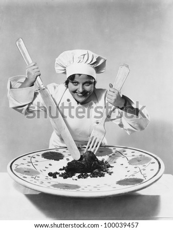 Cook with food on oversize plate with oversize utensils