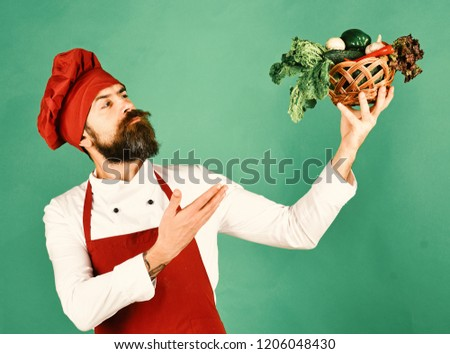 Cook with proud face in burgundy uniform presents vegetables in wicker bowl. Chef holds lettuce, tomato, pepper and mushrooms. Vegetarian restaurant concept. Man with beard on green background.