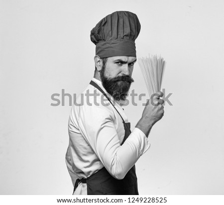 Cook with strict angry face in burgundy uniform holds dry pasta. Catering and italian food concept. Man with beard isolated on white background. Chef holds bunch of spaghetti in hand. #1249228525