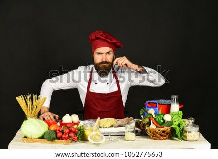 Cook with strict face in burgundy uniform near food. Man with beard sits by countertop on black background. Chef with pasta, vegetables and dough on table curls mustache. Professional cuisine concept. #1052775653